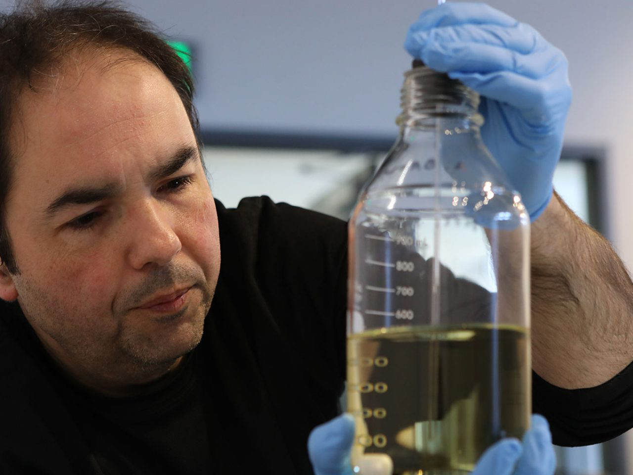 Photo of Adam Brownhead working with a chemical in flask