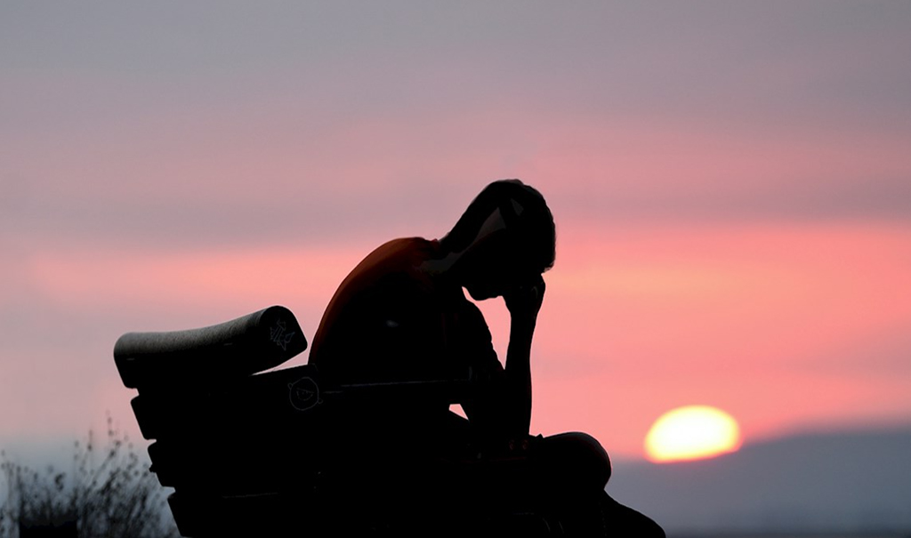 A person sitting with head in hand at sunset.