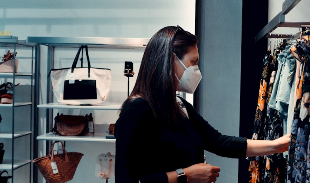 Image of woman wearing a mask while shopping in a boutique.